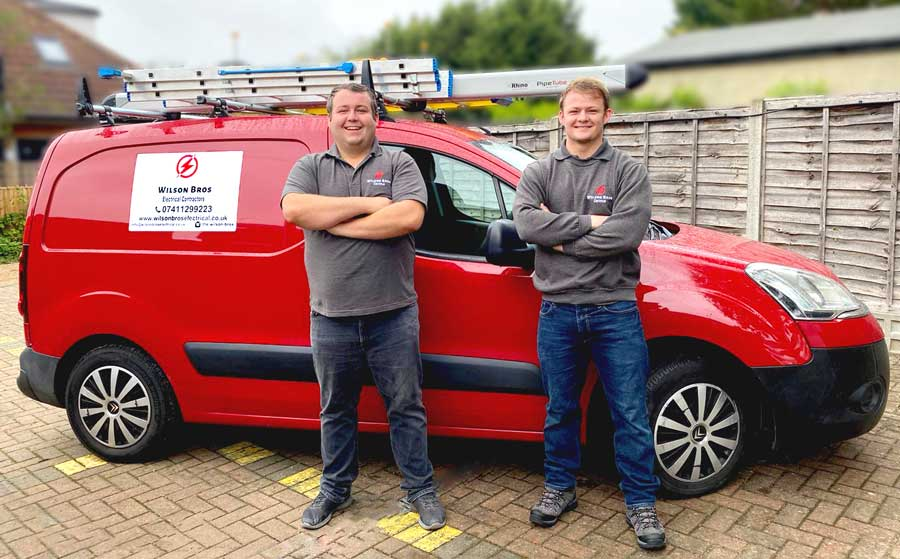 Wilson Brothers of Wilson Bros Electrical in front of their company vehicle